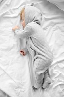Bebezinho de pijama cinza dormindo na cama