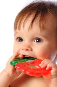 Bebezinho de um ano segura disponível colorido brinquedo de dentição. dentes de criança explodem brinquedo. retrato em fundo branco isolado