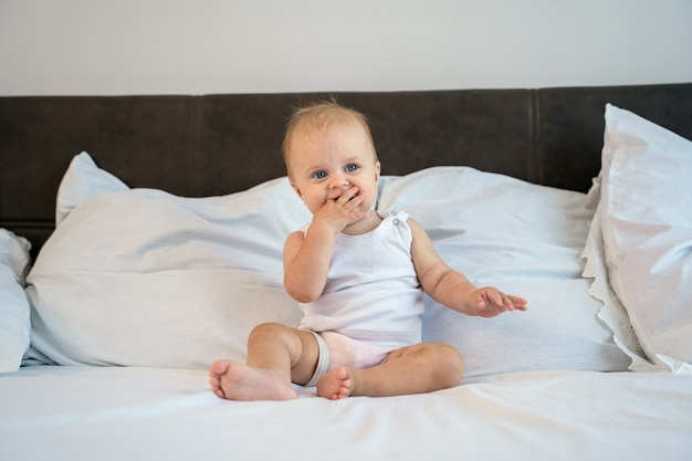 Bebezinho deita-se e regozija-se na cama do quarto em casa