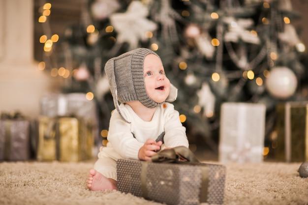 Bebezinho em traje de natal como um coelho branco brincando com caixa de presente