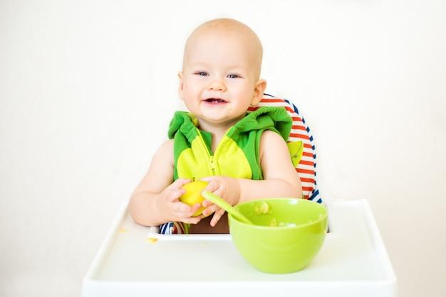 Bebezinho feliz com colher senta-se na cadeira alta e come mingau no prato