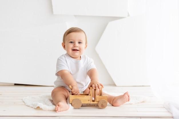 Bebezinho feliz e fofo de seis meses de idade em uma camiseta branca e fraldas, senta-se sobre um fundo claro em casa e brinca com uma máquina de escrever de madeira, espaço para texto
