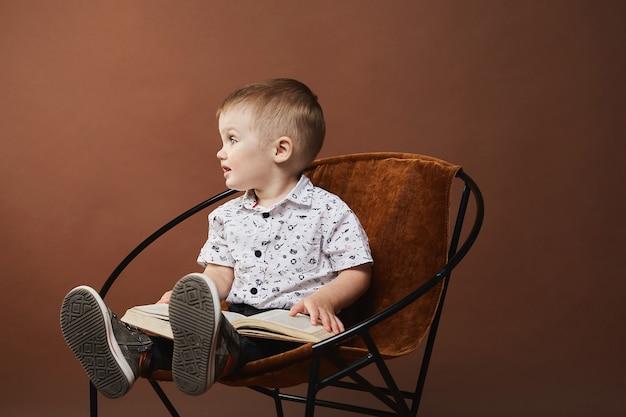 Bebezinho fofo com uma camisa branca e shorts sentado na cadeira com um livro e olhando para o lado