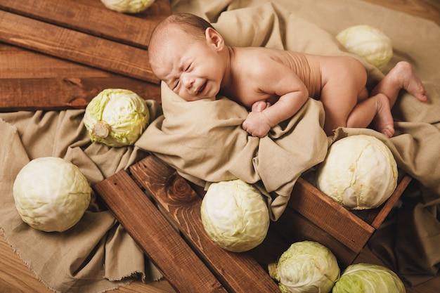Bebezinho fofo deitado na caixa com muitos repolhos por perto