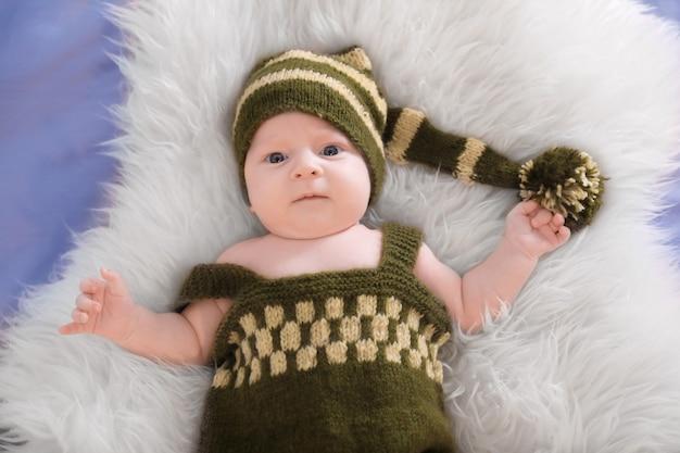 Bebezinho fofo fantasiado de elfo deitado sobre o pelo, vista de cima