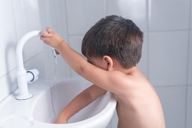 Bebezinho fofo lavando as mãos na pia do banheiro