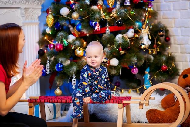 Bebezinho fofo menino sentado no interior de uma casa no fundo da árvore de natal com um presente