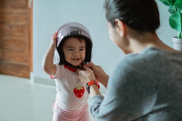Bebezinho fofo usando um capacete com a mãe em casa