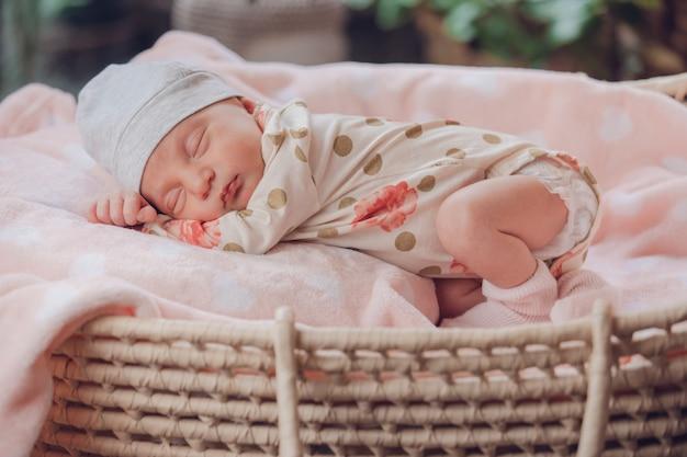 Bebezinho lindo dormindo em uma cesta no cobertor rosa