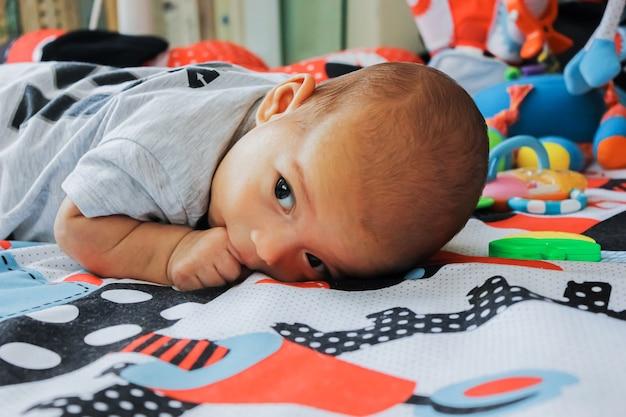 Bebezinho na esteira com brinquedos. criança séria com dedo na boca