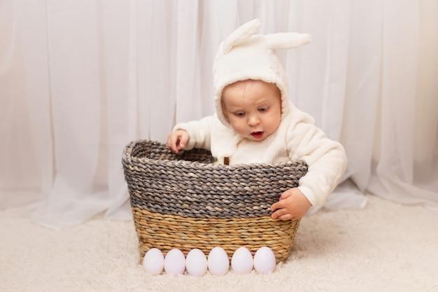 Bebezinho na fantasia de coelho sentado na cesta com ovos de páscoa em casa