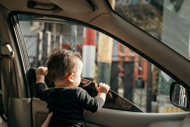 Bebezinho no carro quando as janelas são abertas durante uma viagem de carro