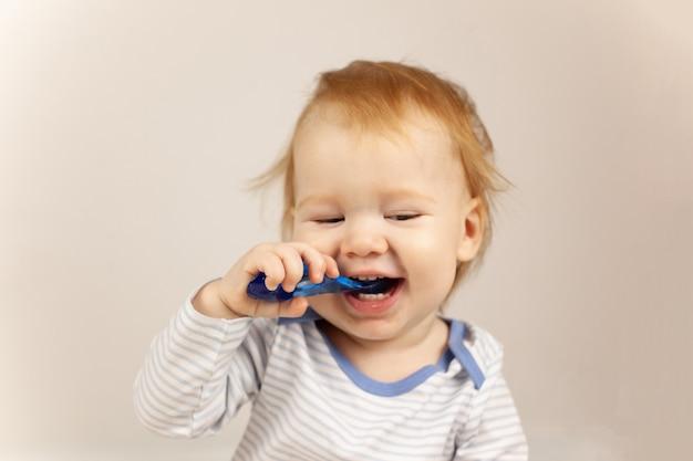 Bebezinho praticando escovar os dentes sozinho.
