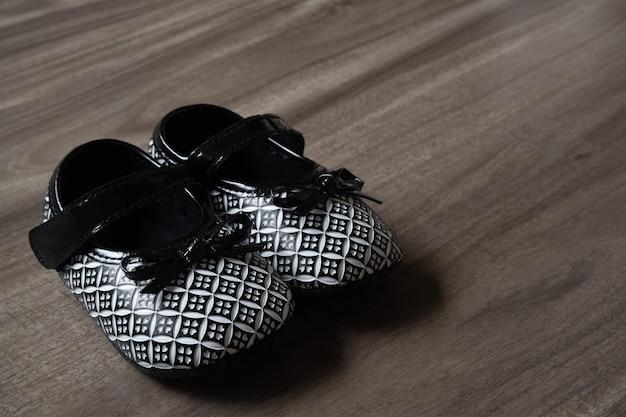 Bebezinho preto e branco crianças sapatos em madeira fundo