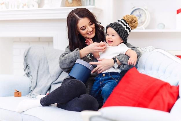 Bebezinho se divertindo com a mãe no sofá azul na sala de natal decorada festiva. feliz férias de inverno conceito.