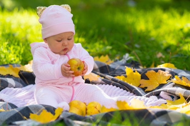 Bebezinho segurando uma maçã de outono, olhando para ela com curiosidade enquanto se senta em um tapete em um gramado no jardim