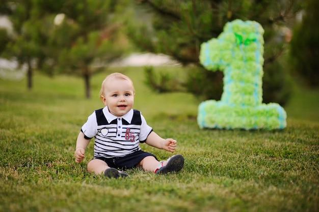 Bebezinho sentado na grama e sorri em seu primeiro aniversário