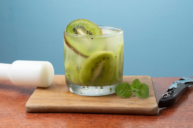 Bebida alcoólica caipirinha à base de coquetel de kiwi em parede azul