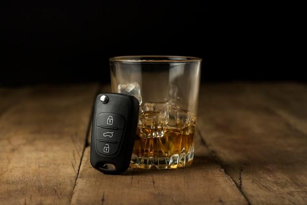 Bebida alcoólica com gelo em um copo e chaves do carro em um fundo de madeira. conceito de condução bêbado, pare de beber e dirigir.