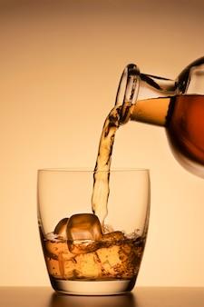 Bebida alcoólica, derramada de um copo de uma garrafa em um fundo laranja dourado. whisky, conhaque ou bourbon scotch.