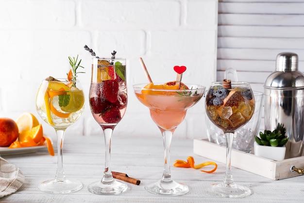 Bebida alcoólica diferente em vidro com acessórios de bar em fundo branco de madeira