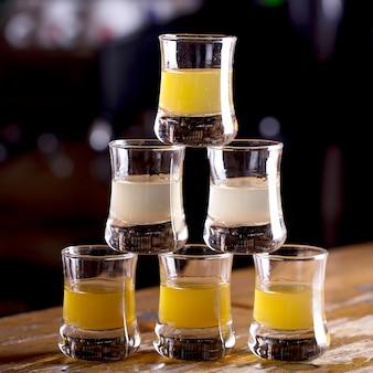 Bebida alcoólica em pequenos copos no bar. tiros na mesa do bar.