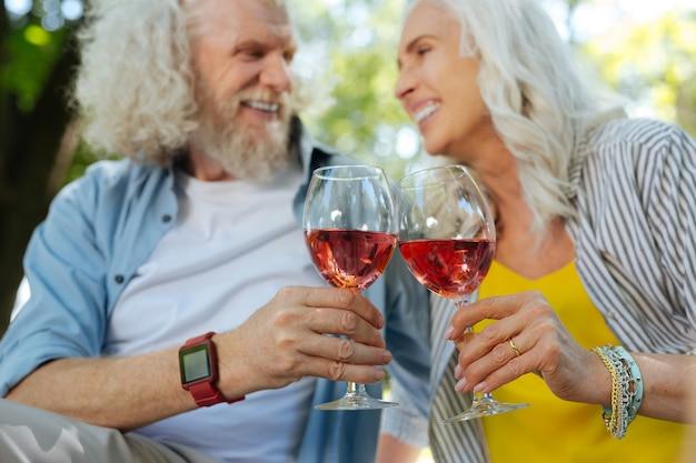 Bebida alcoólica. foco seletivo de taças com vinho sendo batidas por um alegre casal de idosos