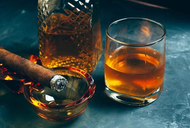 Bebida alcoólica forte, uísque escocês em copo e jarra de moda antiga