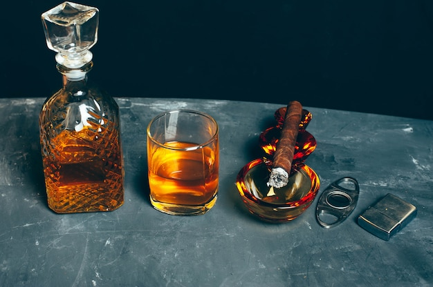 Bebida alcoólica forte, uísque escocês em vidro e jarra com charuto no cinzeiro