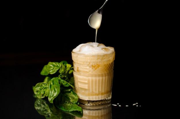 Bebida alcoólica fresca com espuma e gelo em um copo servido na superfície escura com manjericão
