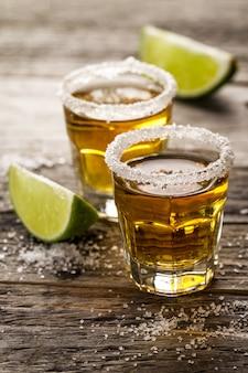 Bebida alcoólica saborosa com tequila com limão e sal no vibrante fundo de mesa de madeira. fechar-se.