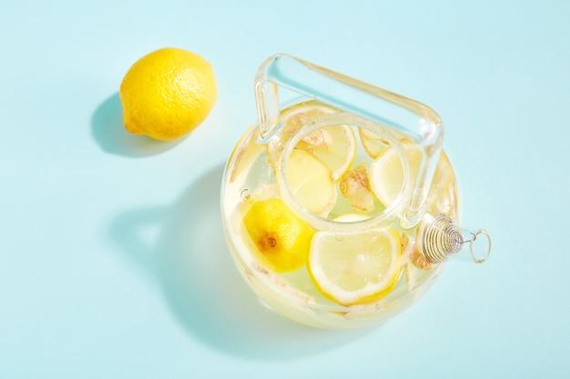 Bebida antivírus com limão e gengibre em uma chaleira transparente e elegante