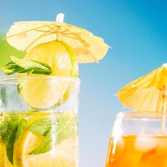 Bebida apetitosa com limão fatiado e raminhos de hortelã no vidro de guarda-chuva decorado