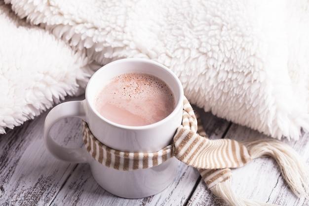 Bebida aquecedora - xícara de cacau com leite na mesa