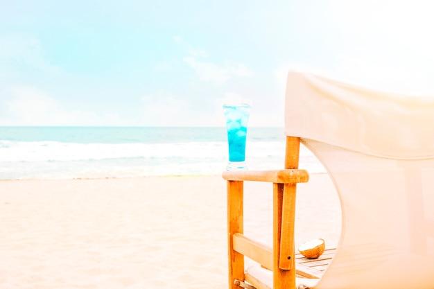 Bebida azul brilhante no braço da cadeira de madeira e coco