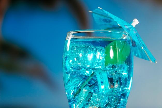 Bebida azul com hortelã em vidro decorado guarda-chuva