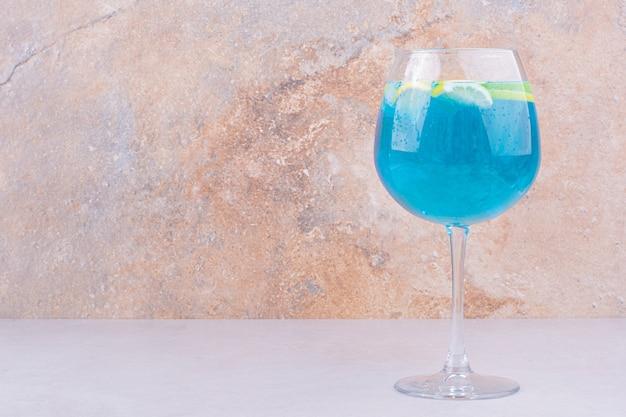 Bebida azul com rodelas de limão na superfície branca
