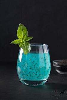 Bebida azul da semente da manjericão com suco tropical no vidro no preto. fechar-se.