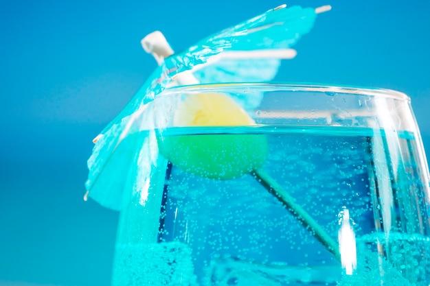 Bebida azul fresca com bolhas de azeite e cubos de gelo