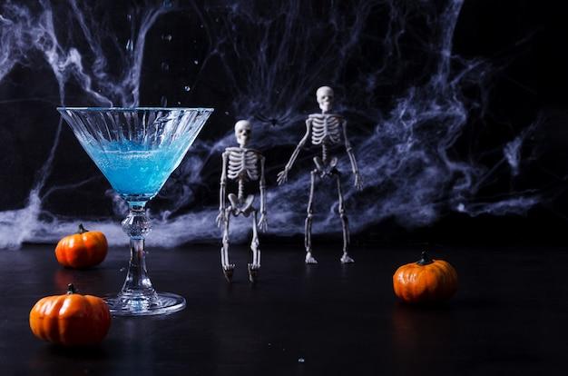 Bebida azul para o halloween, dia de murtos em um fundo preto, no fundo de teias de aranha, esqueletos, abóboras