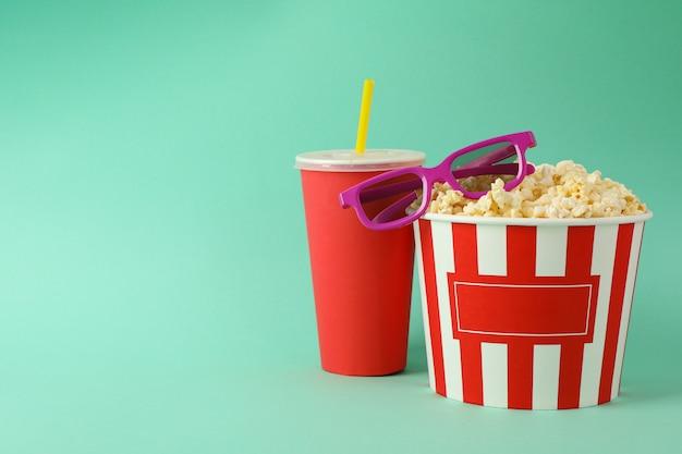 Bebida, balde com pipoca e óculos 3d no espaço de hortelã