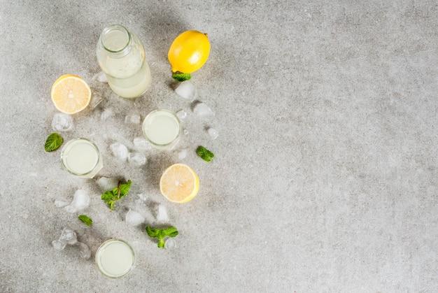 Bebida caseira alcoólica italiana tradicional, limoncello de licor de limão com citros frescos, gelo e hortelã, na mesa de pedra cinza, vista superior