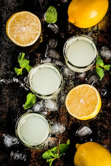 Bebida caseira alcoólica italiana tradicional, limoncello de licor de limão com citros frescos, gelo e hortelã, na mesa preta enferrujada, vista superior