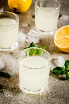 Bebida caseira alcoólica italiana tradicional, limoncello de licor de limão com frutas cítricas, gelo e hortelã, na mesa de pedra cinza