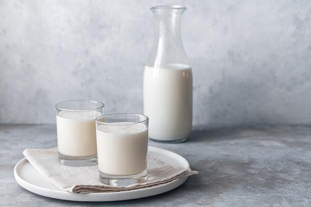 Bebida caseira simples de leite fermentado - iogurte de kefir comassi em dois copos em uma parede cinza