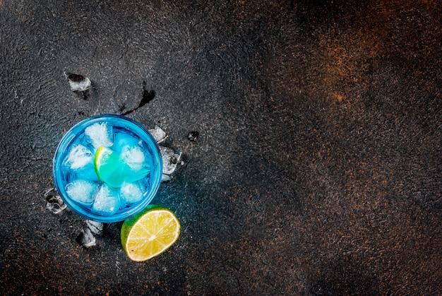 Bebida colorida de verão, bebida gelada de coquetel de álcool de lagoa azul com limão e hortelã