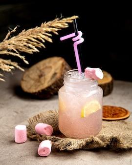 Bebida com gás rosa clara com fatia de limão, guarnecida com marshmellow