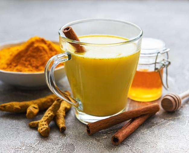 Bebida com leite de açafrão amarelo. leite dourado com canela, açafrão, gengibre e mel sobre fundo cinza de concreto.