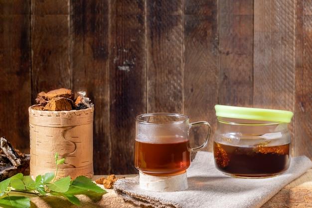 Bebida cura de chaga de cogumelo de bétula, pedaços de cogumelos, galho na prancha de madeira no pano de fundo de madeira velha. copie o espaço.