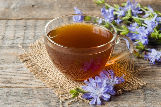 Bebida da chicória no copo e flores no fundo de madeira rústico. planta medicinal cichorii.